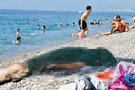 Plajdaki cenazeye aldırmadan güneşlendiler