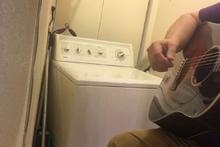 Çamaşır makinesiyle beraber müzik yapan adam