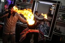 Müşterilerini ateşle traş ediyor