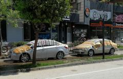 Adanalılar dolu yağışından zarar görmemek için otomobilleri kilimle kapladı