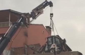 Kepçeyi yıkacağı binanın üstüne vinç ile yerleştirdiler