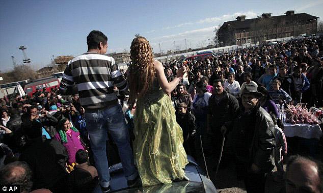 Burada kızlarını satıyorlar -5-Bu yıl Bulgaristan'ın kuzeyinden ve Plovdiv, Pasardzhik, Sliven ve Jambol gibi şehirlerden 2000 kişi bu etkinliğe katıldı. Yeni evlenen çift eski bir arabanın üstünde göbek atarken, bu iki kardeş güzel yemeklerin ve dansın keyfini çıkartıyor.