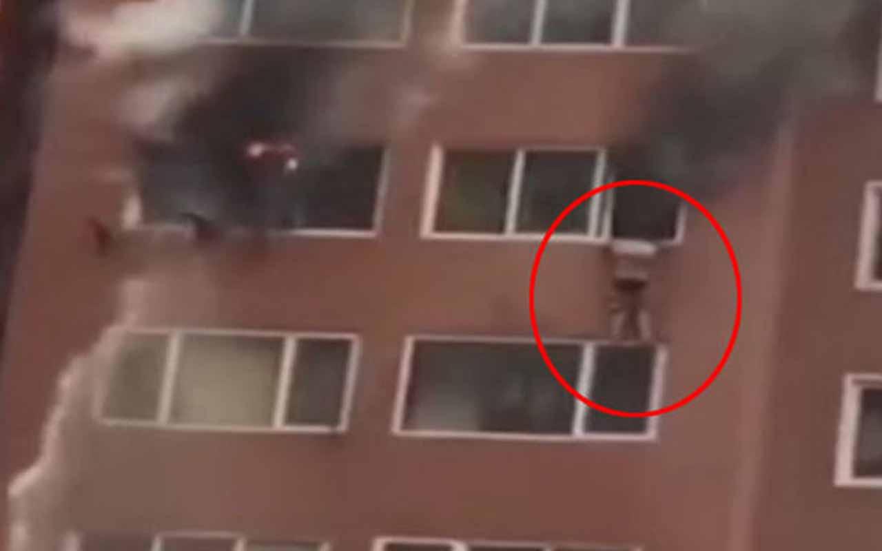 Evi yanan kadın, pencereden sarkarak kurtarılmayı bekledi