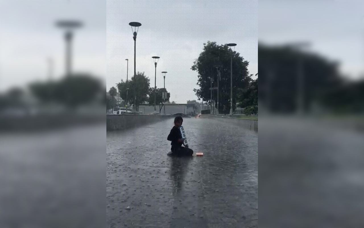 İstanbul'da sağanakta melodikasını çalmaya devam eden çocuk