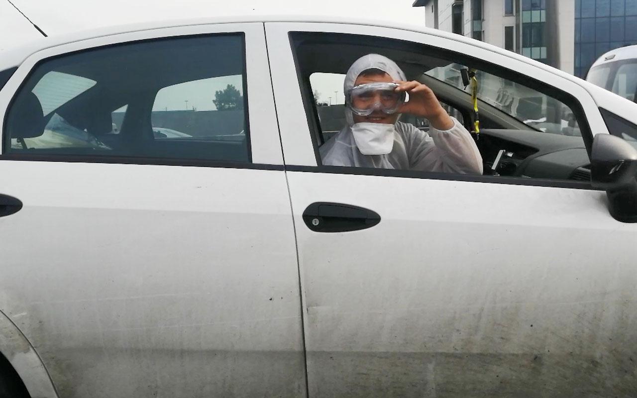 İstanbul'da otomobil içinde koronavirüse karşı tulum maske ve gözlük
