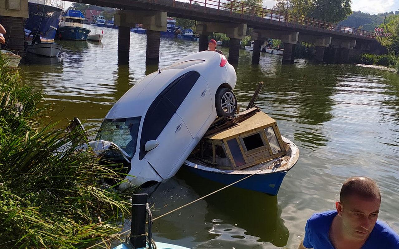 Otomobil, nehir kenarındaki teknenin üzerine düştü